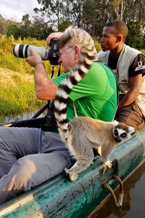 main next to lemur with camera