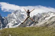 person jumping in front of mountain